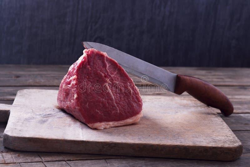 Biftecks de boeuf noirs principaux crus frais d'Angus Tenderloin sur la planche à découper en bois avec un couteau image stock