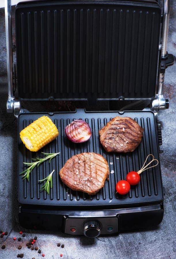 Biftecks de boeuf rôtis et légumes grillés sur le gril électrique photographie stock libre de droits