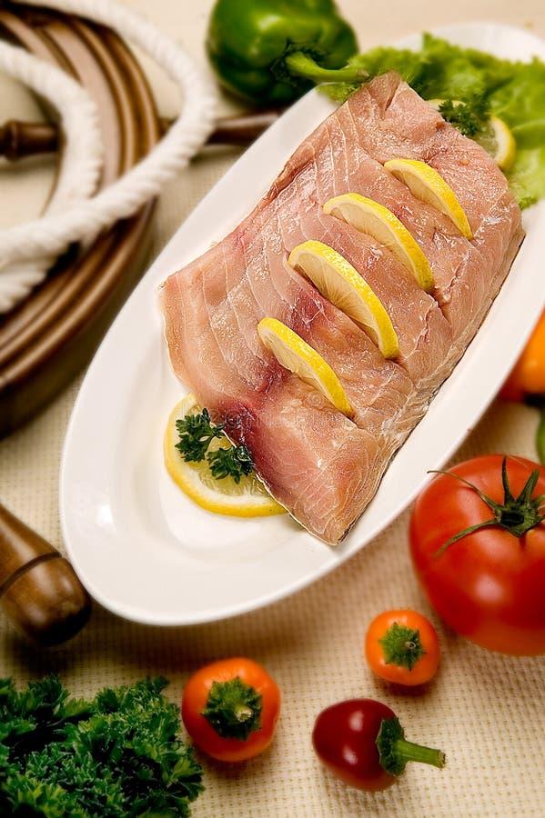 Biftecks de poisson cru marinant pour le gril ou faisant cuire d'un plat avec le citron et les épices image stock