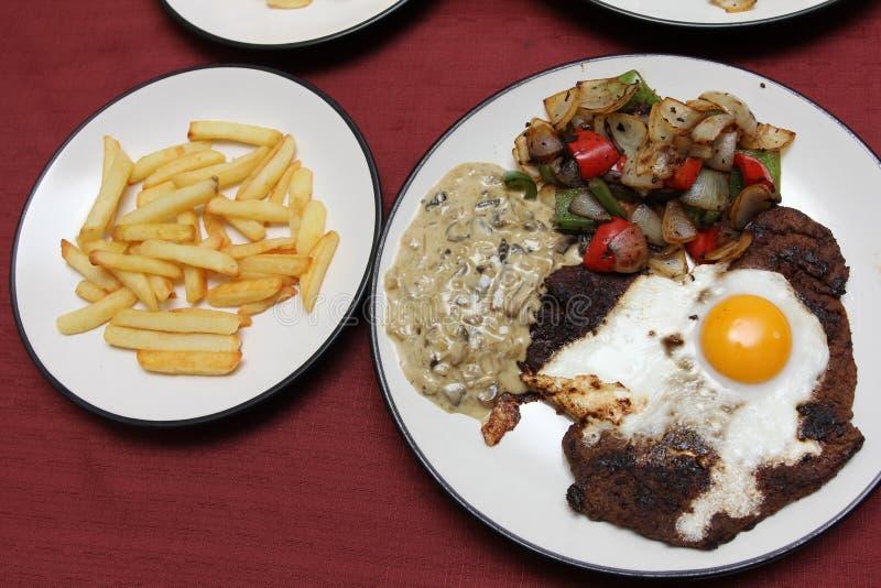 Biftecks et oeufs avec la sauce aux champignons et les fritures photo stock