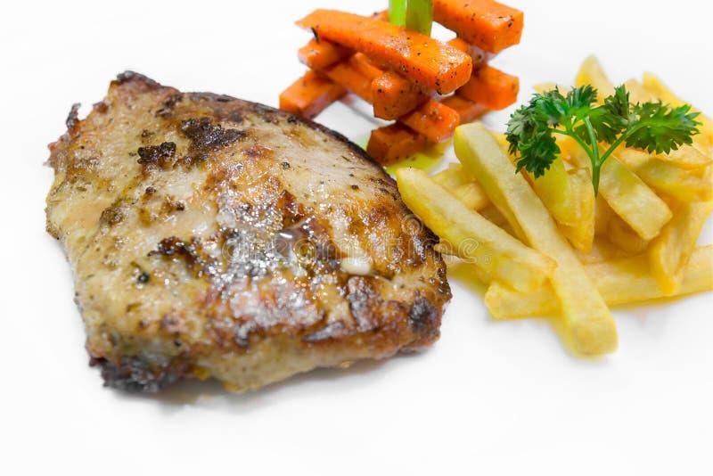 Biftecks grillés d'échine de porc, service avec des pommes frites et légumes images libres de droits