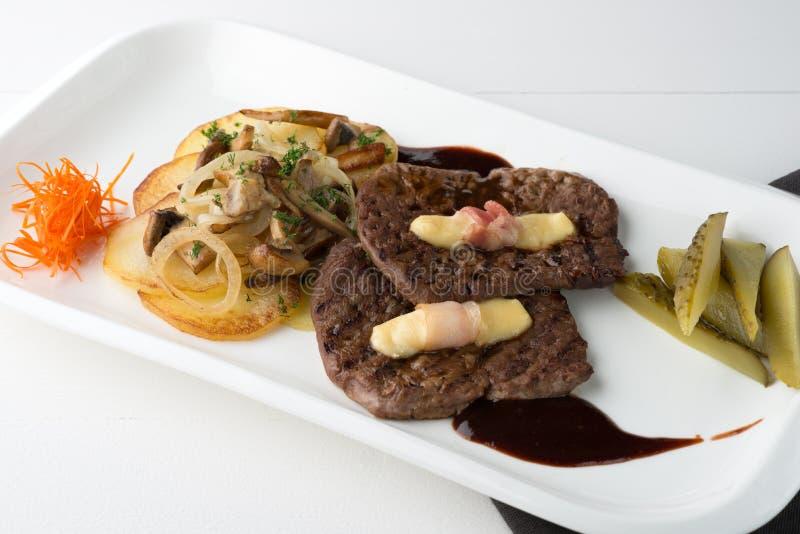 Biftecks grillés de viande avec des légumes, des conserves au vinaigre, la sauce et la décoration images libres de droits