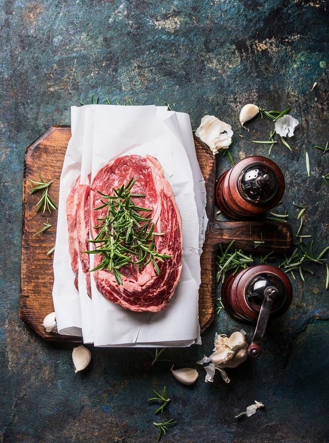 Biftecks marbrés crus de viande avec le papier d'emballage sur la planche à découper rustique avec les moulins frais d'assaisonne photos libres de droits