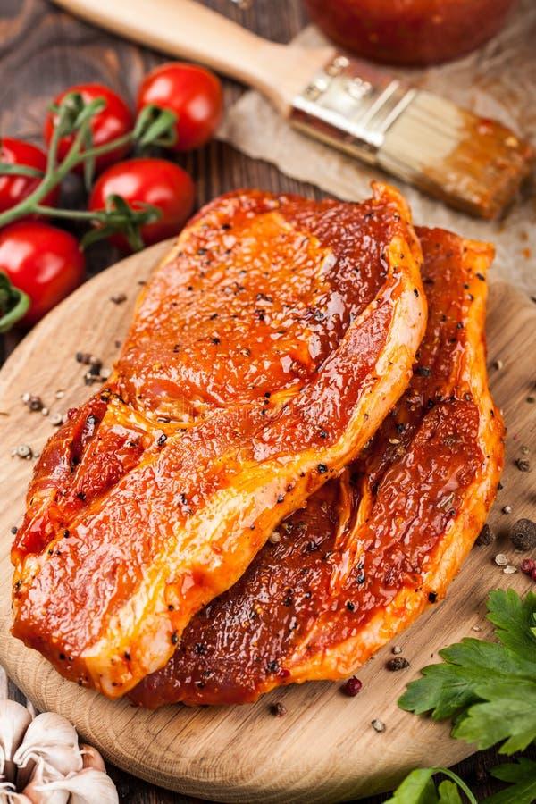 Biftecks marinés de porc sur la planche à découper image stock