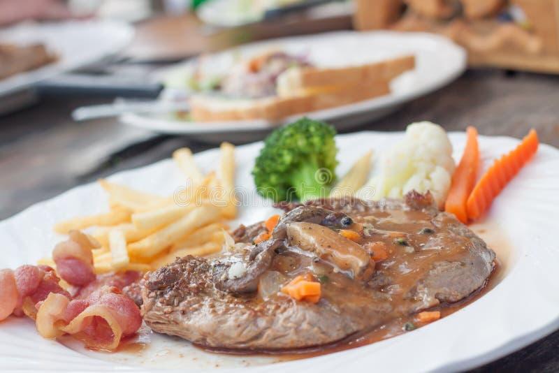 Biftecks, pommes frites, lard et légume grillés photos stock