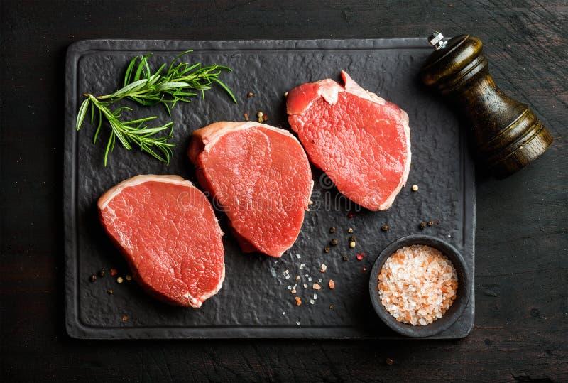 Biftecks ronds d'oeil cru de boeuf avec les épices et le romarin photographie stock