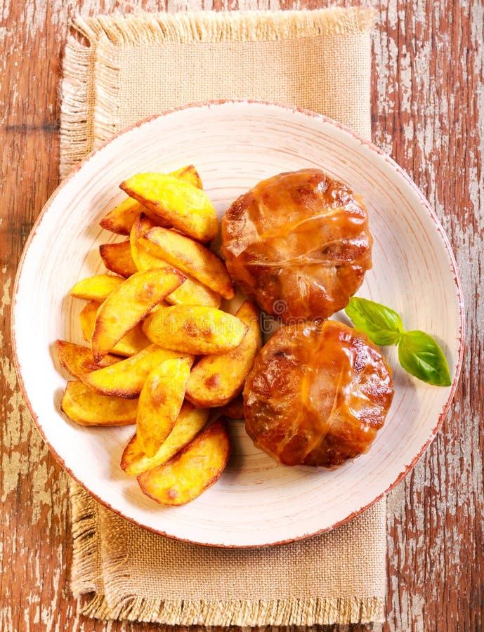 Bifteks enveloppés en pomme de terre de lard et de rôti image libre de droits