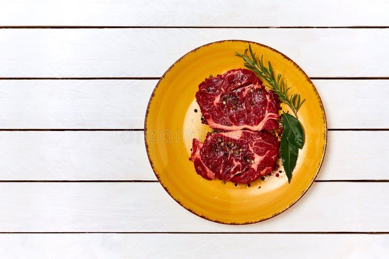 Bifteks, romarin et poivre crus de plat jaune Copiez l'espace photographie stock libre de droits