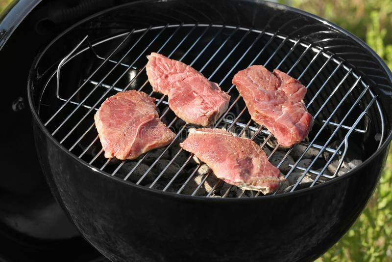 Bifteks savoureux faisant cuire sur le gril de barbecue dehors, photographie stock libre de droits