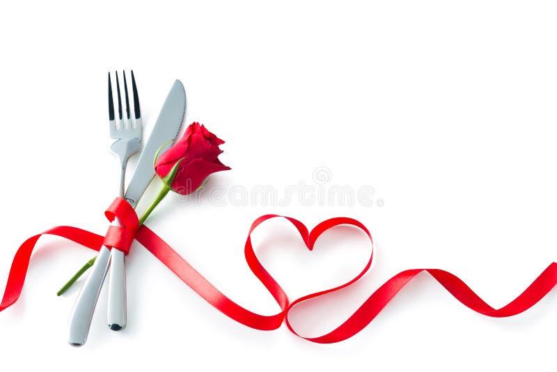 Bifurcación de la tarjeta del día de San Valentín, cuchillo, cuchara, cubiertos con el corazón rojo s de la cinta fotografía de archivo