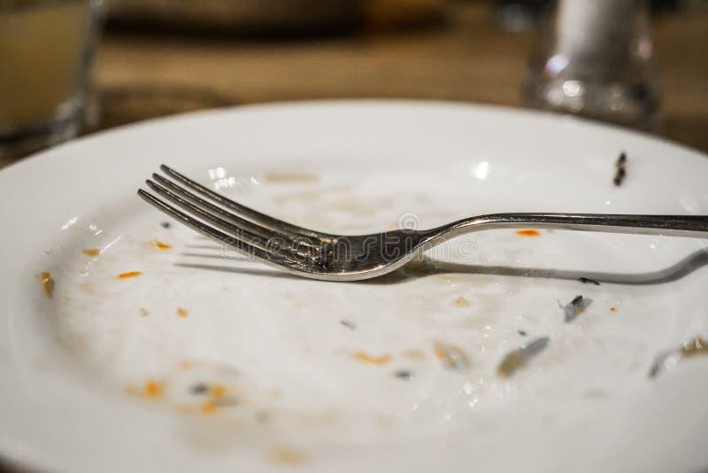 Bifurcación en una placa después de una comida Placa sucia con los rastros de comida en la tabla fotografía de archivo libre de regalías