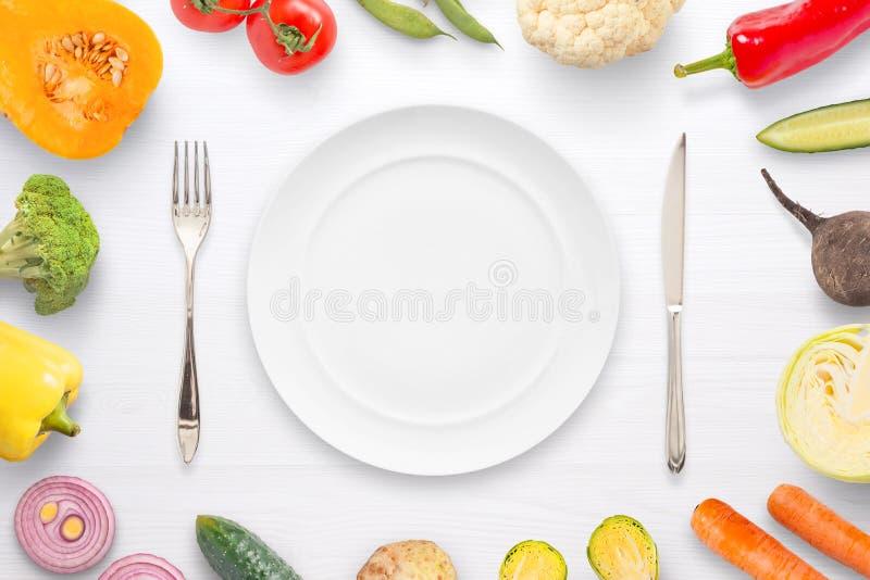 Bifurcación vacía y cuchillo de la placa rodeados con las verduras imagen de archivo