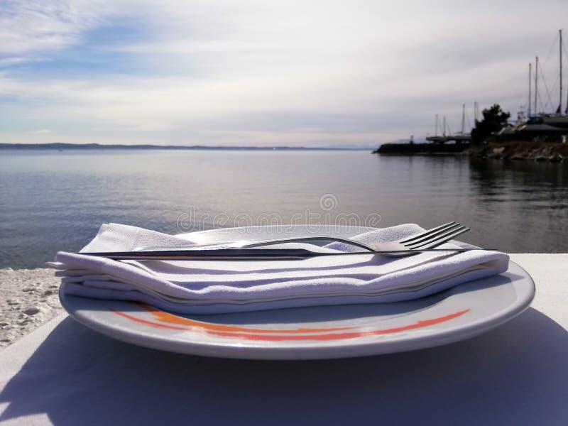 Bifurcación y cuchillo en la servilleta en la placa que está en la opinión del mar de la tabla imágenes de archivo libres de regalías