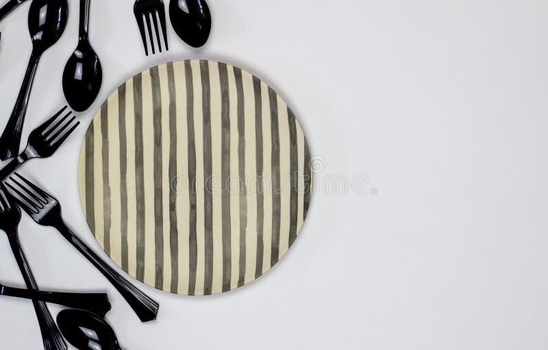 Bifurcaciones y cucharas al lado de la placa en un fondo blanco Concepto m?nimo imágenes de archivo libres de regalías