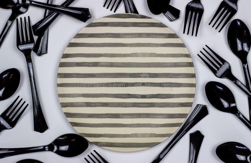 Bifurcaciones y cucharas al lado de la placa en un fondo blanco Concepto m?nimo imagen de archivo libre de regalías