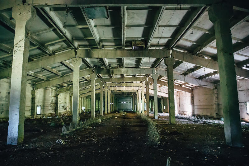 Big abandoned industrial warehouse interior inside, perspective stock photography