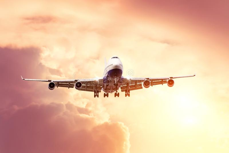 Big airplane approaching landing in the evening sky.  stock photo