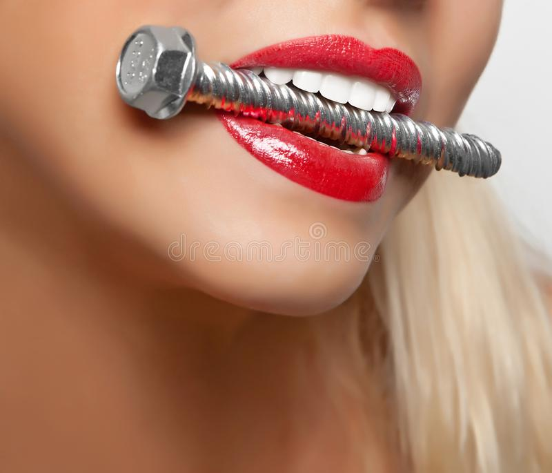 Big anchor bolt in the girl`s teeth with red lipstick painted lips. stock photo
