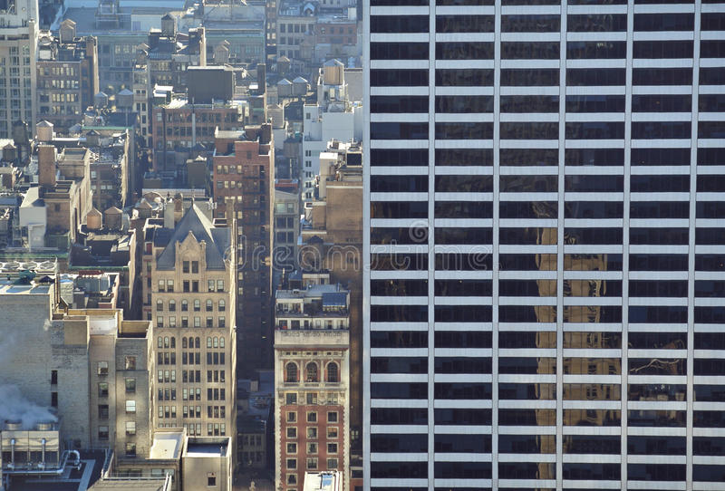 Big apple contrast. Big building against smaller ones in New York royalty free stock photos