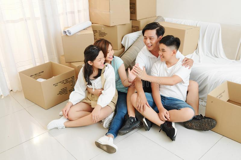 Family settling in new house. Big Asian family of parents and teenage kids celebrating moving in new house royalty free stock image