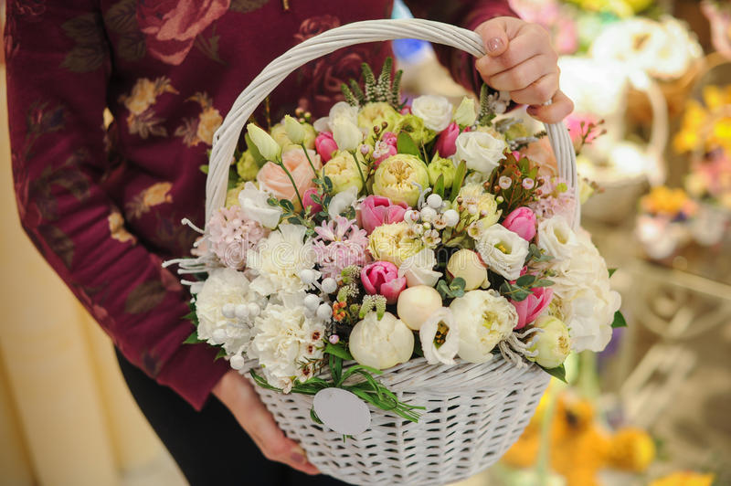 Big basket with white light flowers bouquet. In hands royalty free stock images