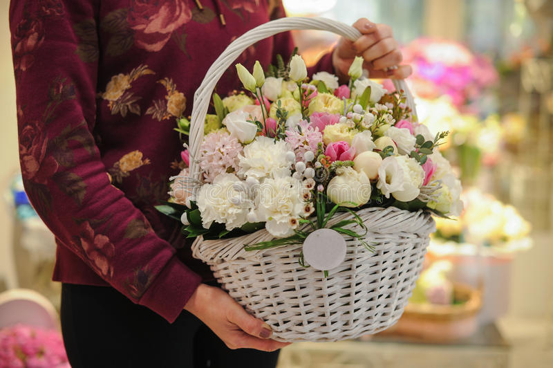 Big basket with white light flowers bouquet. In hands stock images