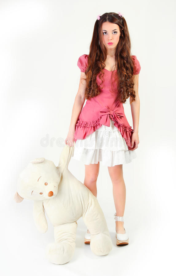 Big bear. Cute young woman dressed as a doll holding big bear royalty free stock image