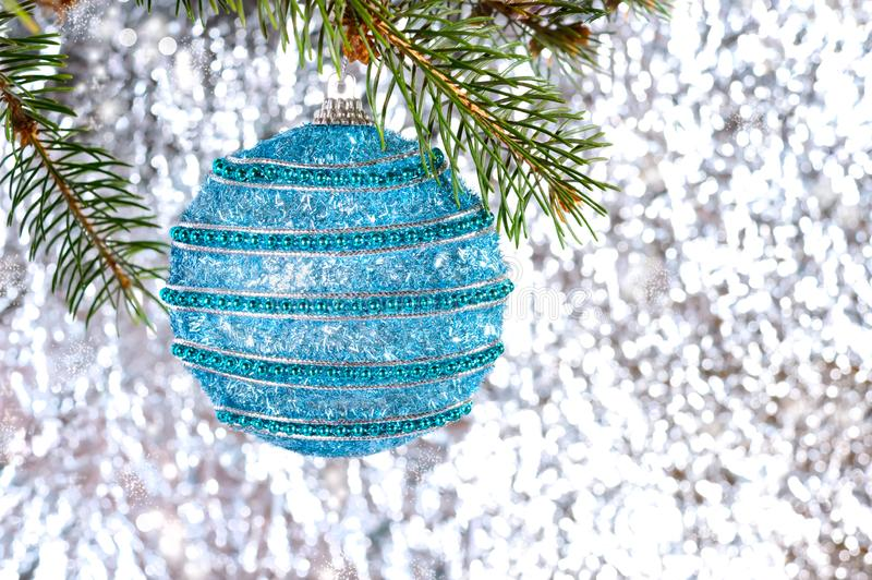 Big beautiful blue ball, green branch of spruce on a light blurred background royalty free stock photos