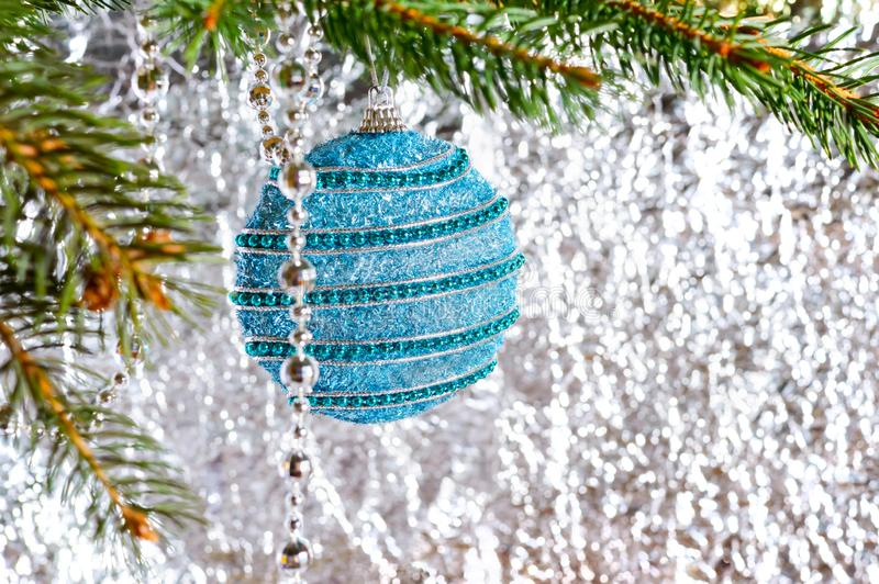 Big beautiful blue ball, green branch of spruce on a light blurred background. stock photography