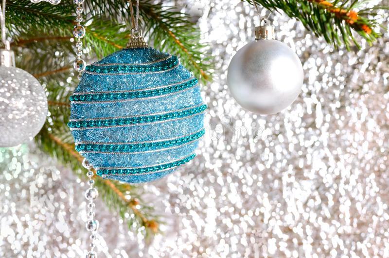 Big beautiful blue ball, green branch of spruce on a light blurred background royalty free stock images