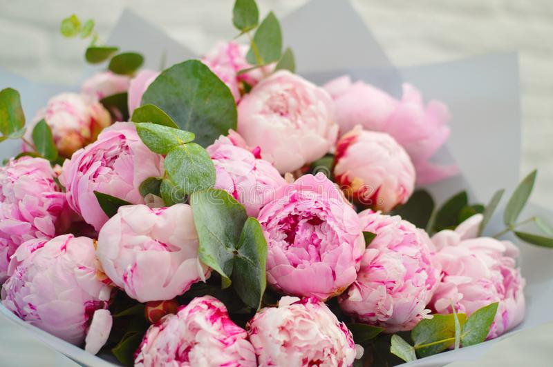 Big beautiful bouquet of pink peonies. In stylish modern packing on a white table. Concept of flower shop. Romantic bouquet for a postcard for a holiday a stock photo