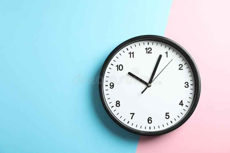 Big beautiful office clock on two tone solid color. Pink and light blue background stock photography