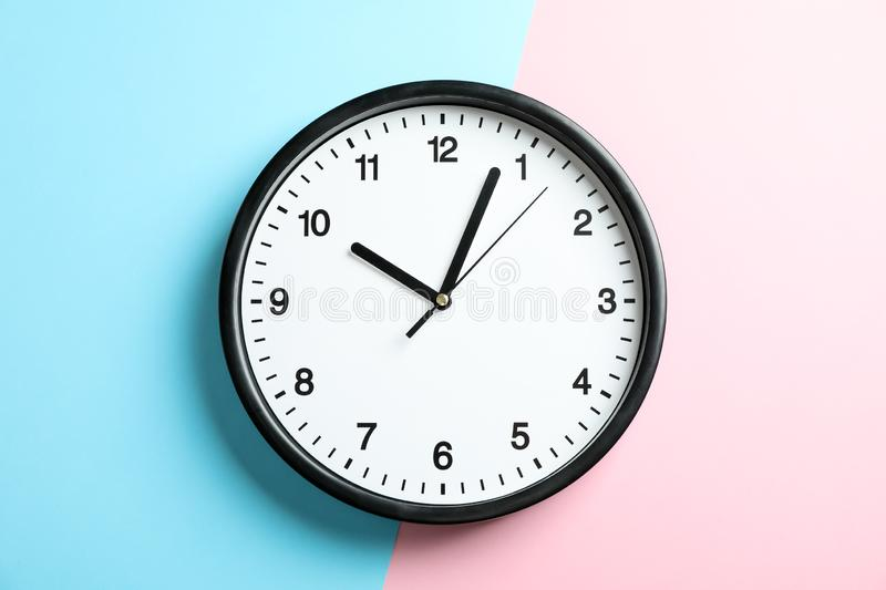 Big beautiful office clock on two tone solid color. Pink and light blue background stock photo