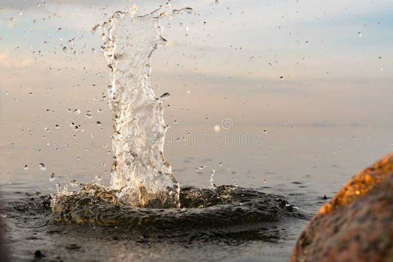 Big beautiful splash of water in the sea at sunset. natural desktop background. Beautiful splash of water in the sea at sunset. natural desktop background stock image