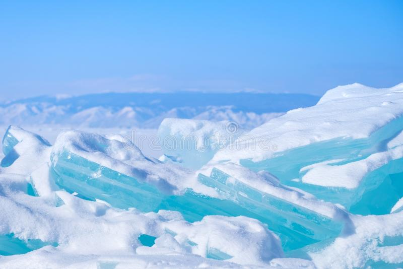 Big Beautiful turquoise blue ice on the Frozen Lake Baikal with mountains on the background. stock images
