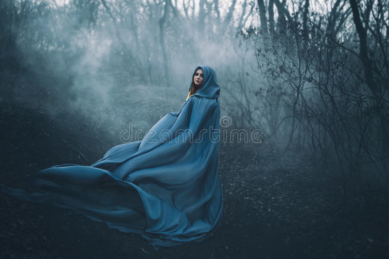 A big, beautiful woman in a blue raincoat royalty free stock photos