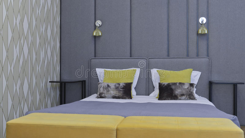 Big bed in a modern luxury apartment bedroom, in grey royalty free stock photos