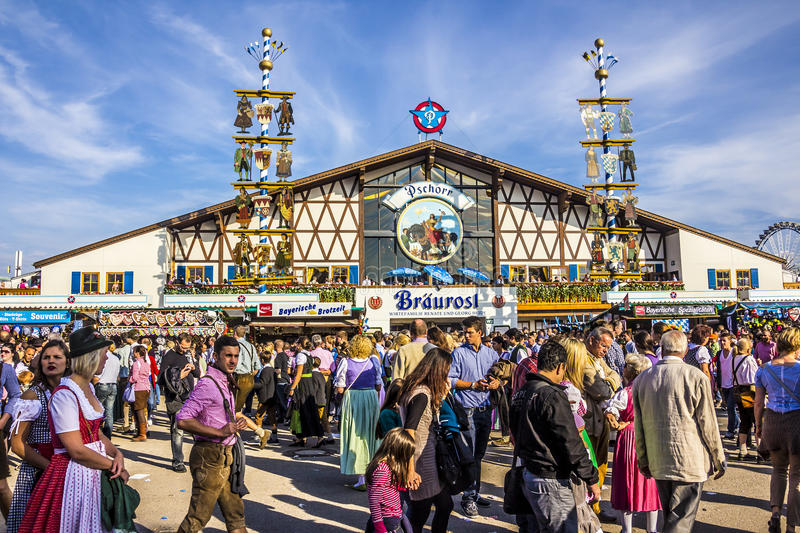 Big beer tent. Oktoberfest, Munich: One of the big beer tents. In the foreground, people are walking along, partly dressed in traditional costumes royalty free stock photo