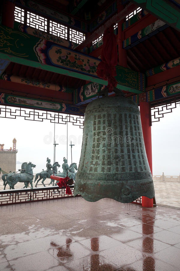 Big bell at Chengshantou Scenic Area near Weihai, China. Weihai, China – July 31, 2014: Big bell under roof with traditional patterns at Chengshantou stock photo