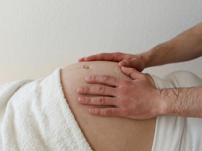 Big belly of a pregnant woman who lies in white clothes on her back. On the stomach are male hands. Close-up royalty free stock photography