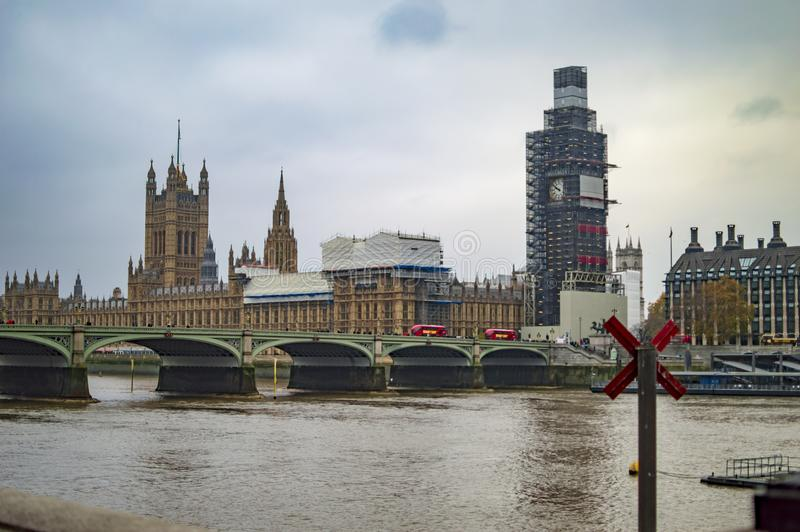 Big ben across the river thames with crossed pole. In london stock photo