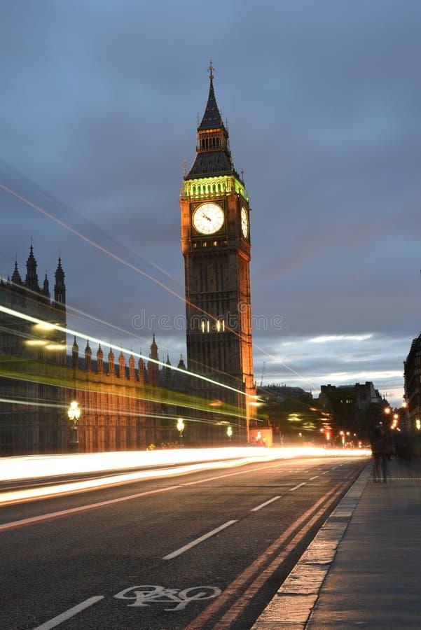 Big Ben eller stor klockatorn eller slott av Westminster eller UK-parlamentet på natttimmar med ljusa slingor av bussar, bilar royaltyfria foton