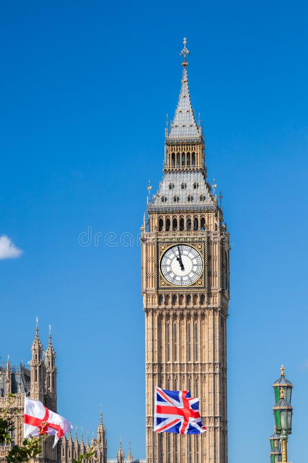Big Ben with flags of England in London, UK royalty free stock photo