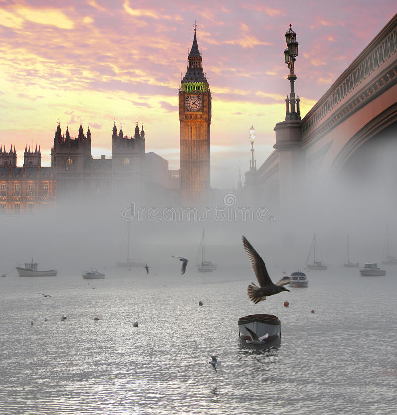 Big Ben, London, UK. Big Ben with bridge durind a foggy morning with flying birds, Westminster, London, UK stock photos