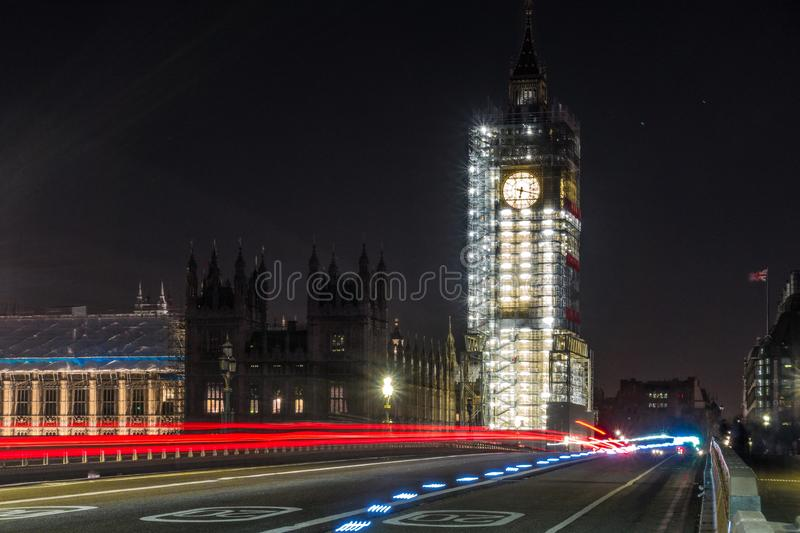 Big ben at night. At this time the tower was under construction. There are also light trails from cars royalty free stock photos