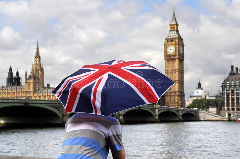 Big Ben and tourist with British flag umbrella in London. Big Ben and tourist with British flag umbrella looking down River Thames in London stock images