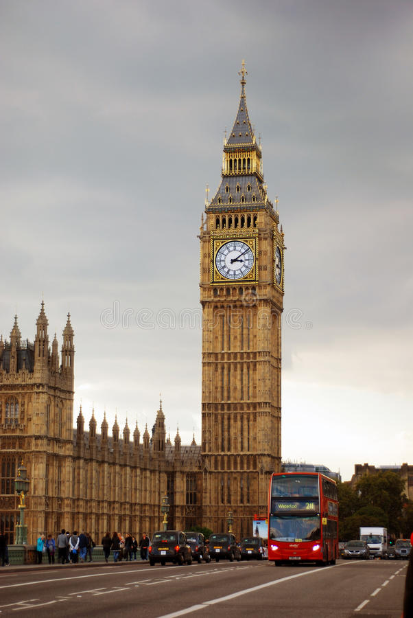 Big Ben Tower Near City Road With Bus and Cars Traveling Under Gray White Clouds royalty free stock images