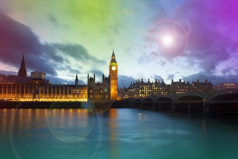 Big Ben and Westminster palace in London at night. Abstract colorful image with lens flare stock photos