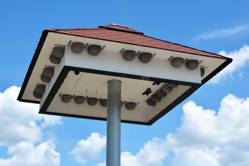 Big bird house with nest boxes under roof in front of blue sky stock image