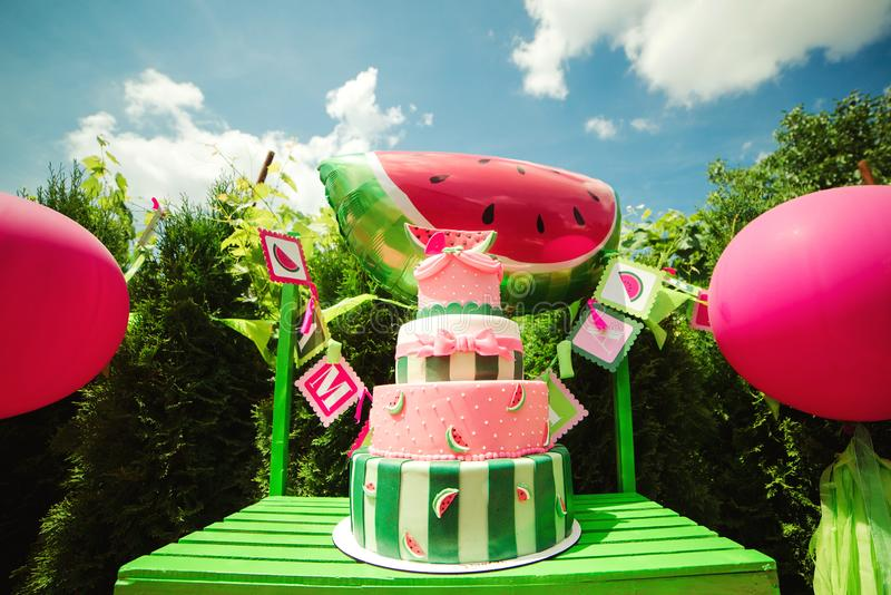 Big birthday cake on a sweet table in backyard. Family celebrating a child`s birthday outdoors. Summer party for daughter royalty free stock photo